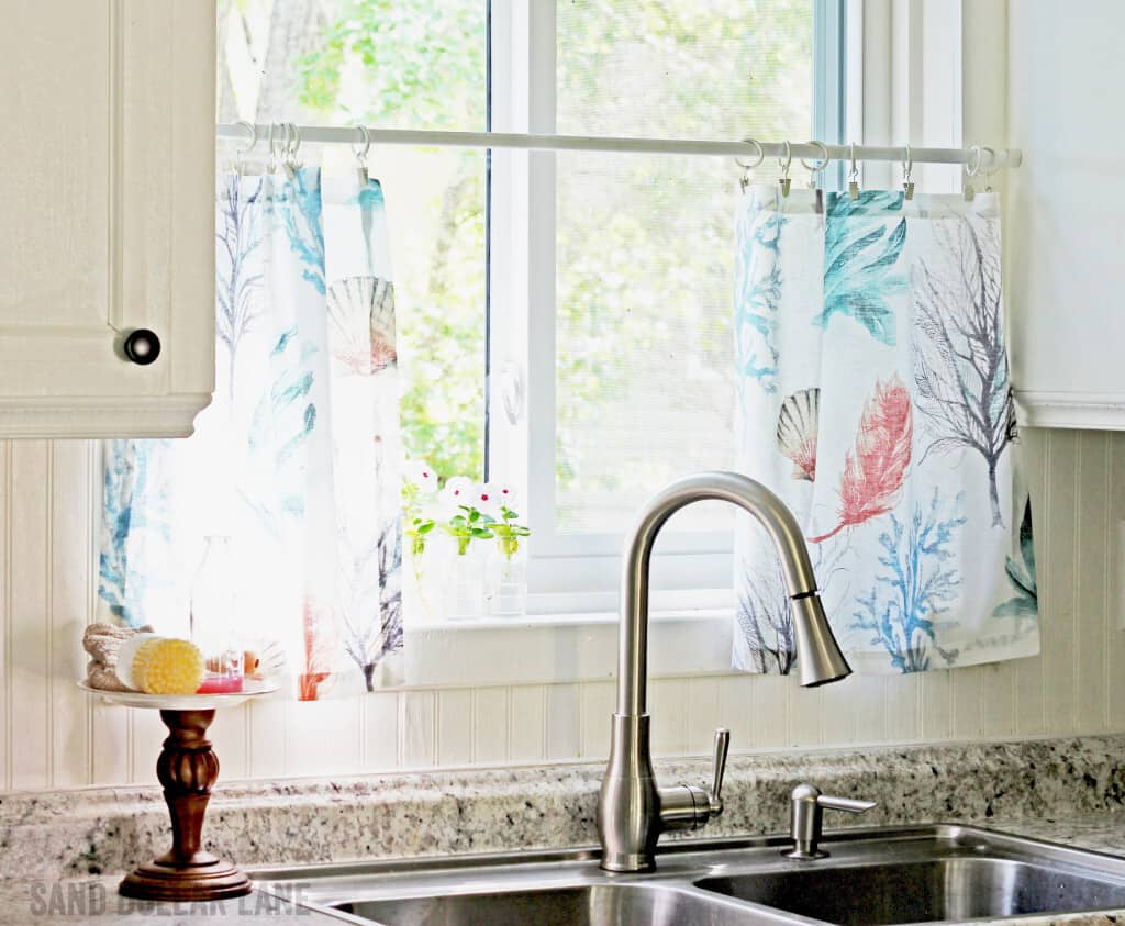 Cute Pottery Barn napkins make cute coastal style curtains in this pretty famhouse style kitchen