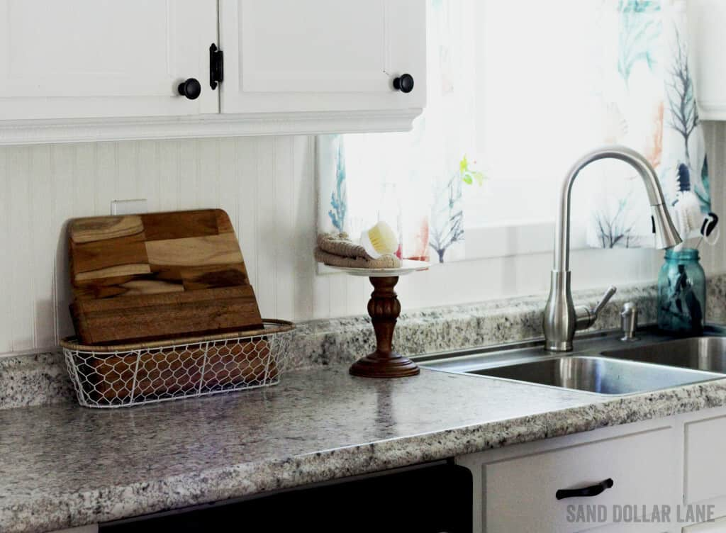 Wooden cutting boards in basket and dish washing tolls in coastal famhouse kitchen