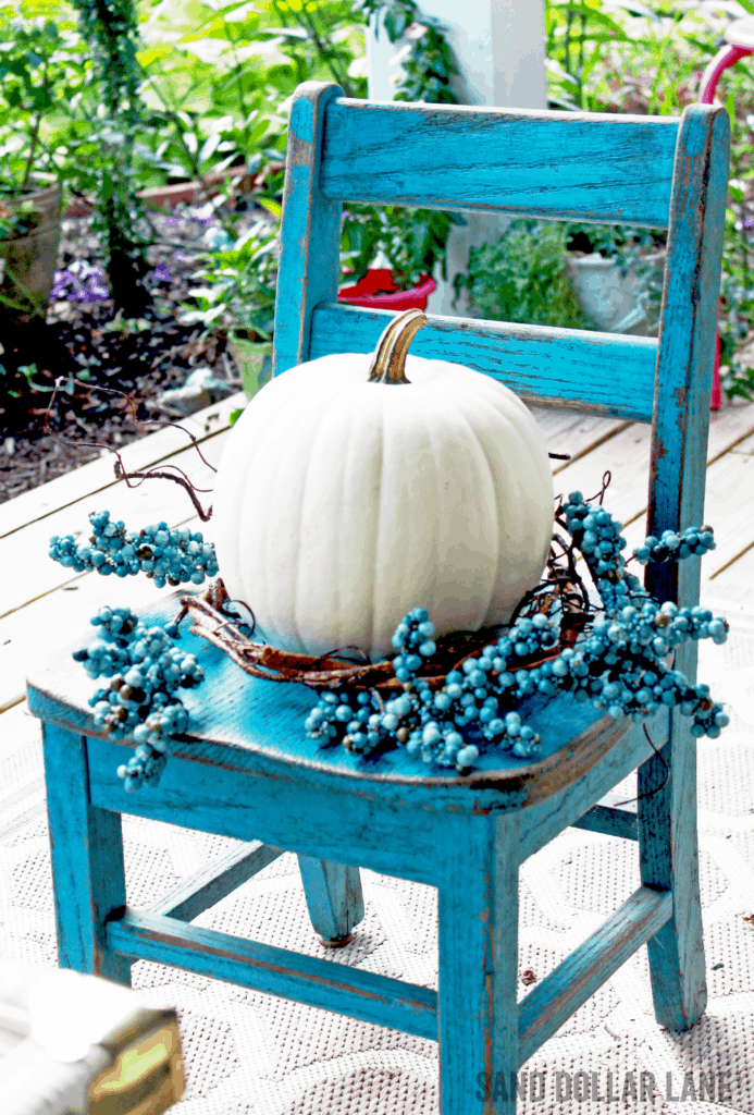 cute white pumpkin on vintage turquoise student chair