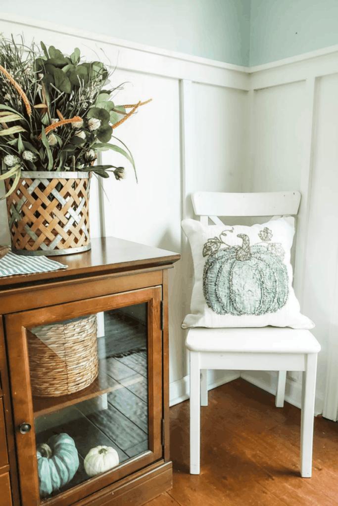 white chair with pumpkin pillow