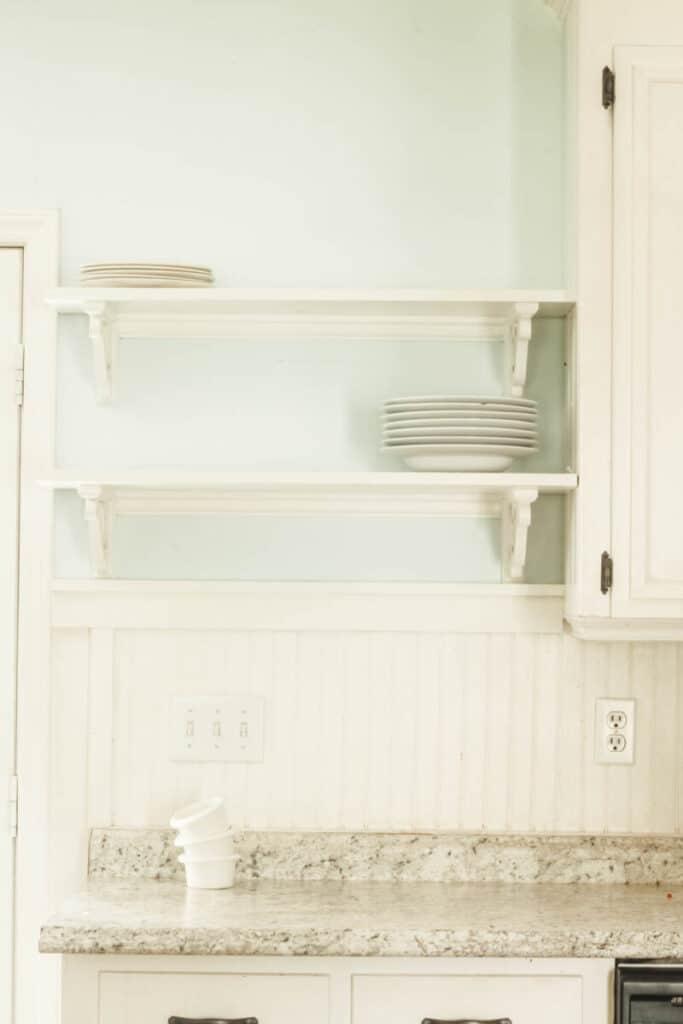 open kitchen shelves with white plates
